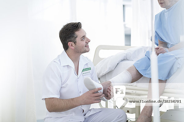 Nurse caring for senior patient in hospital bed