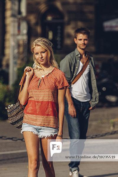 Porträt einer jungen Frau  die auf der Straße geht  während ihr Freund im Hintergrund steht.