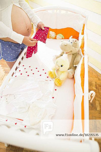 Schwangere neben einem Kinderbett Schwangere neben einem Kinderbett