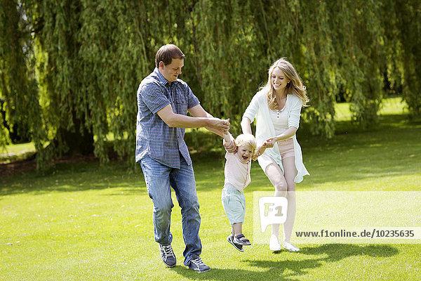 Eltern spielen mit ihrem kleinen Sohn im Park