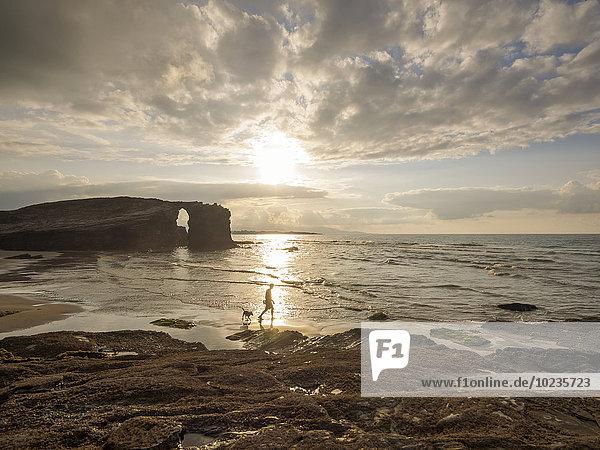 Spanien,  Galizien,  Ribadeo,  Playa de Aguas Santas bei Sonnenuntergang,  Person und Hund am Strand