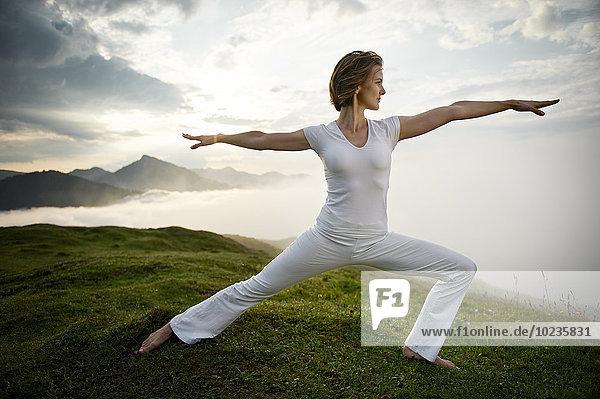 Österreich  Kranzhorn  Mittlere erwachsene Frau beim Yoga auf dem Berggipfel