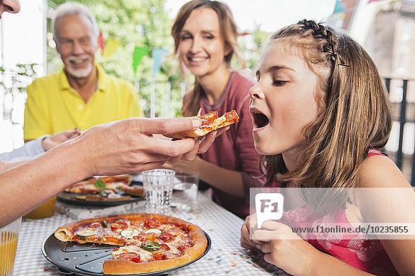 Mädchen wird auf der Familienfeier mit hausgemachter Pizza gefüttert.