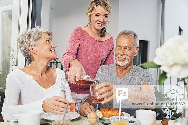 Erwachsene Tochter beim Frühstück mit ihren Eltern auf dem Balkon