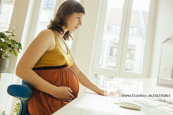 Eine schwangere Frau  die in ihrem Heimbüro arbeitet.