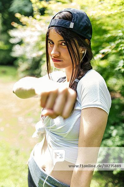 Porträt einer jungen Frau mit Baseballmütze mit Faust