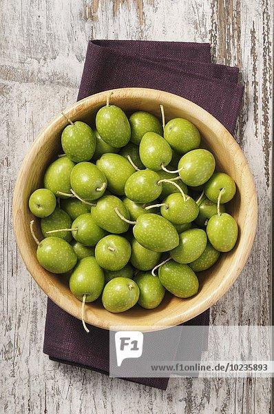Frische grüne Oliven in Holzschale
