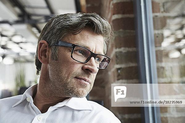 Geschäftsmann mit aus dem Fenster schauender Brille