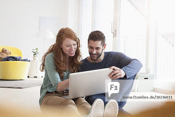 Lächelndes junges Paar sitzt auf dem Boden im Wohnzimmer mit Laptop