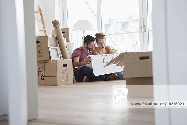 Junges Paar in neuer Wohnung mit Pappkartons im Grundriss