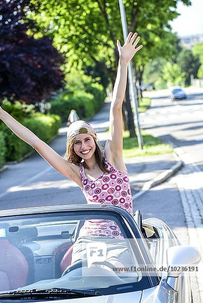 Porträt einer glücklichen jungen Frau  die in einem Cabrio sitzt.