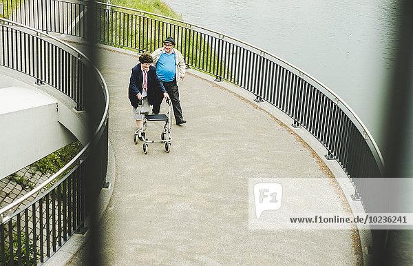 Seniorenpaar mit Gehstock und Rollator auf einer Brücke