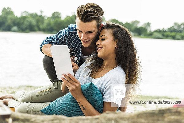 Lächelndes junges Paar mit digitalem Tablett im Freien