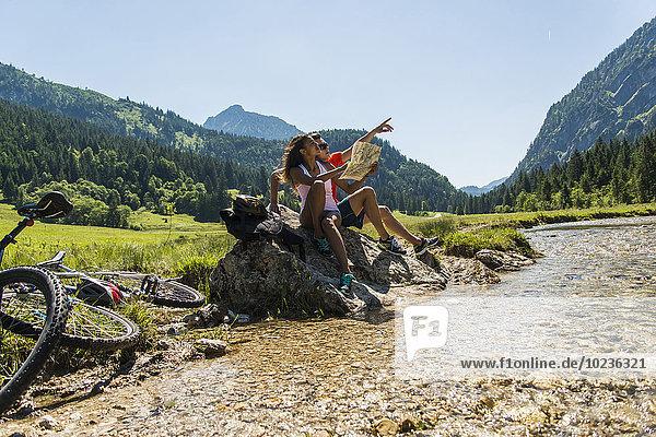 Österreich  Tirol  Tannheimer Tal  junges Paar mit Mountainbikes und Karte am Bach sitzend