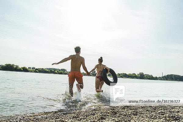 Junges Paar läuft mit Innenrohr im Fluss