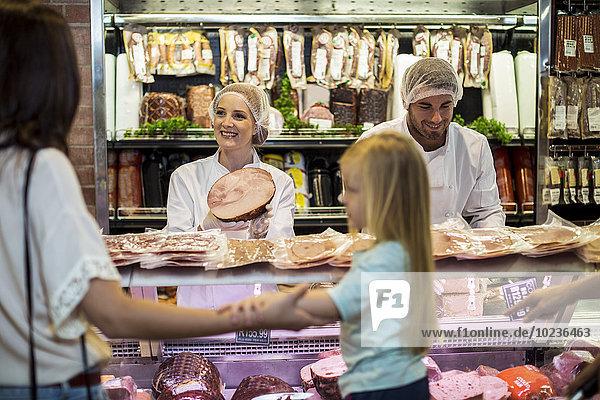 Kunde mit Tochter beim Schinkenkauf in der Metzgerei