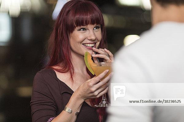 Porträt einer lächelnden jungen Frau mit Cocktailglas  die mit einem jungen Mann flirtet.