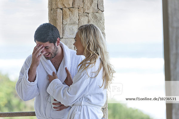 Happy young couple wearing bathrobes in beach house