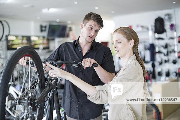 Junger Verkäufer und Kunde beim Betrachten von Fahrrädern