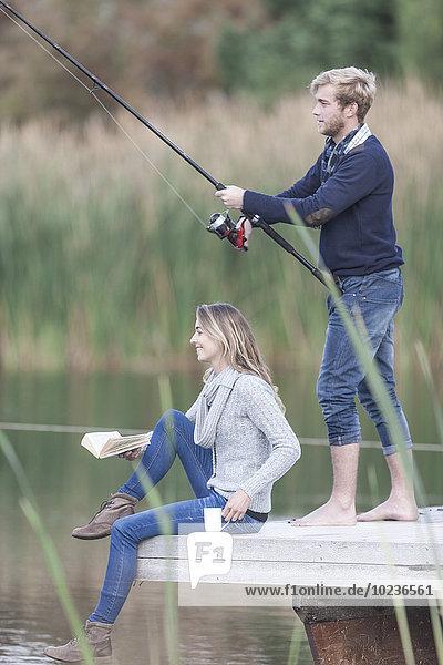 Junges Paar mit Buch  Tasse und Angelrute auf einem Steg am See