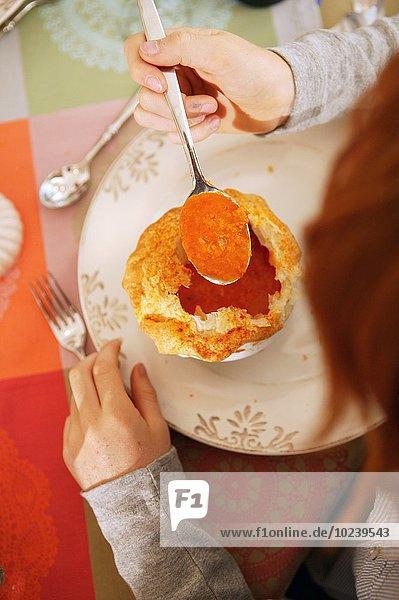 Kind isst Tomatensuppe mit Blätterteighaube