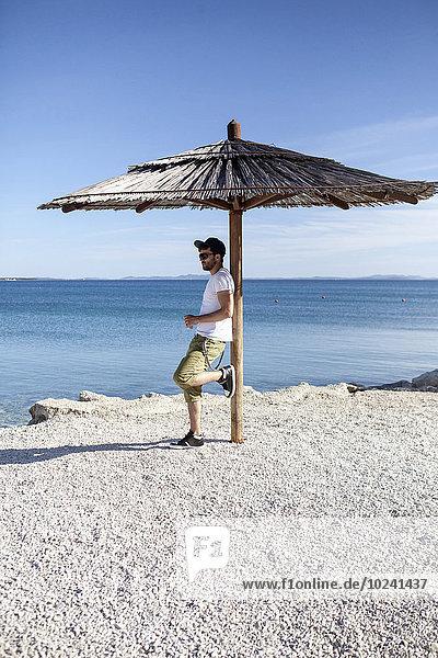 stehend Mann Strand unterhalb Sonnenschirm Schirm jung