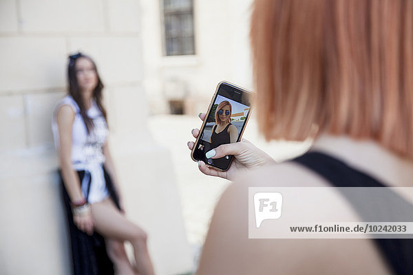 Young woman taking picture of girlfriend