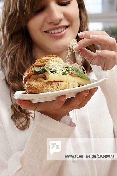 Frau Gemüse Käse Sandwich essen essend isst Croissant Schinken Türkei