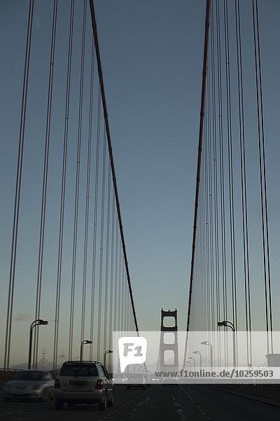 Autos auf der Golden Gate Bridge gegen den klaren Himmel in der Dämmerung