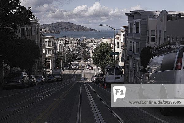Autos auf der Stadtstraße entlang von Gebäuden geparkt