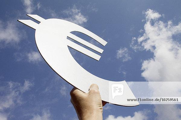 Niedriger Blickwinkel auf die Hand des Menschen  die das Euro-Symbol gegen den Himmel hält.