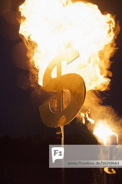 Metallisches Dollarzeichen bei Nacht in Brand gesetzt