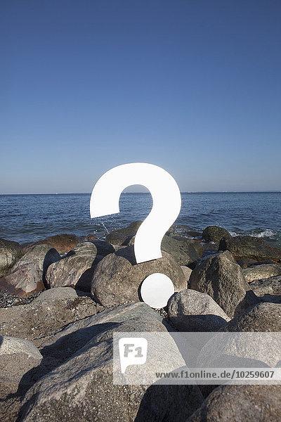 Fragezeichen-Symbol auf Felsen am Meer gegen klaren blauen Himmel