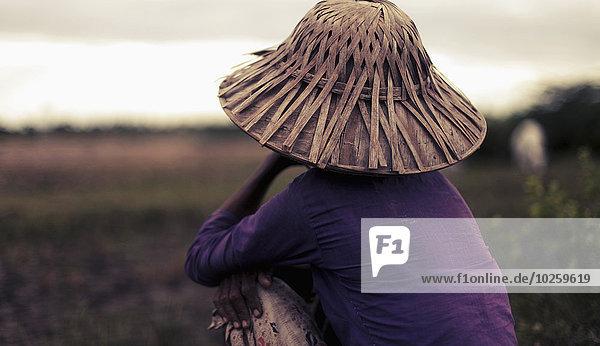 Rückansicht der Frau mit Bambushut auf dem Feld  Region Bago  Myanmar