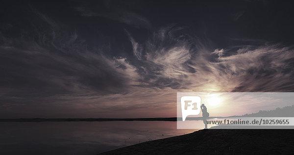 Silhouette Mann am Seeufer bei Sonnenuntergang  Aydar See  Usbekistan