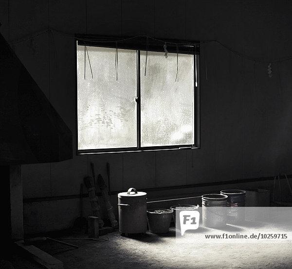 Reihe von Containern pro Fenster im verlassenen Raum