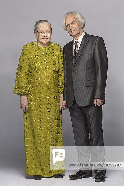 Vollständiges Porträt eines glücklichen älteren Paares auf grauem Hintergrund