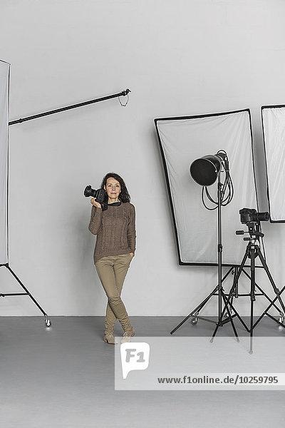 Volle Länge der reifen Fotografin mit Kamera im Fotostudio
