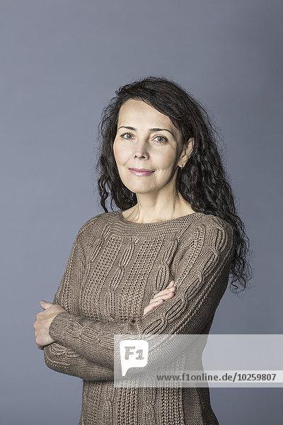 Porträt einer selbstbewussten reifen Frau  die über grauem Hintergrund steht.