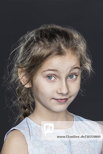 Porträt des selbstbewussten Mädchens über grauem Hintergrund