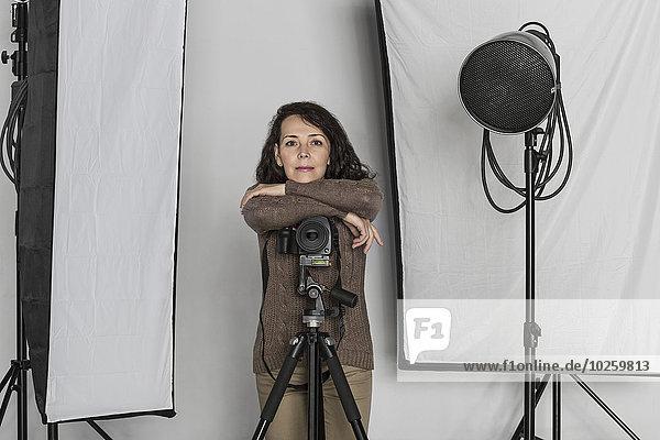 Porträt einer selbstbewussten,  reifen Fotografin,  die sich im Fotostudio auf ein Kamerastativ stützt.
