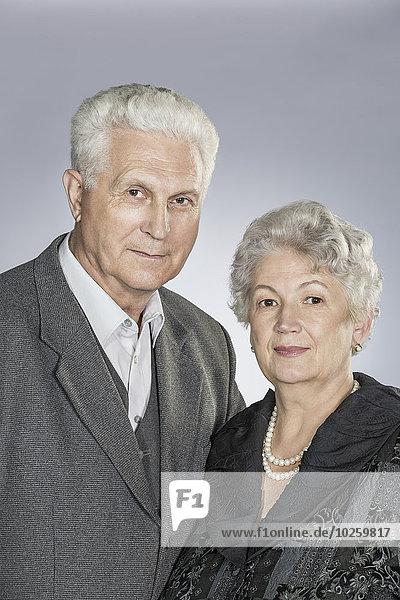 Porträt eines älteren Paares vor grauem Hintergrund