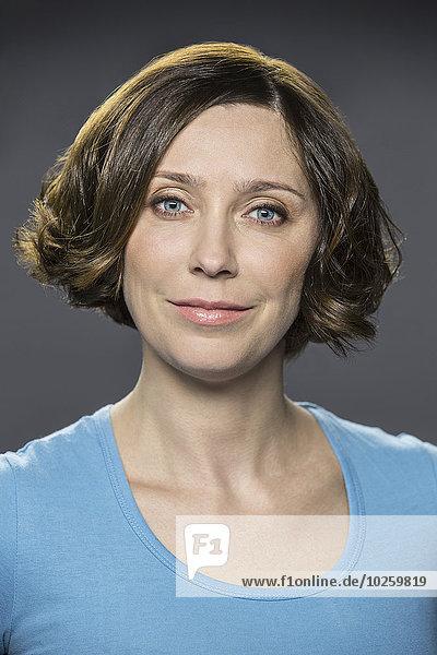 Porträt einer glücklichen mittleren erwachsenen Frau über grauem Hintergrund