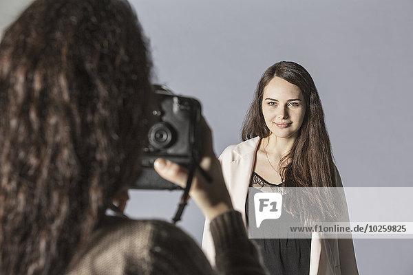 Fotografin fotografiert Mode-Modell über grauem Hintergrund