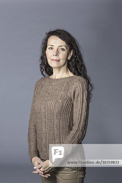 Porträt einer fröhlichen reifen Frau  die auf grauem Hintergrund die Hände umklammert.