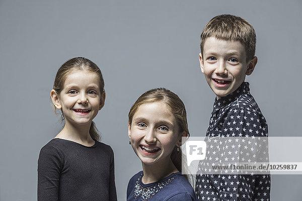 Porträt eines lächelnden Bruders mit Schwestern über grauem Hintergrund