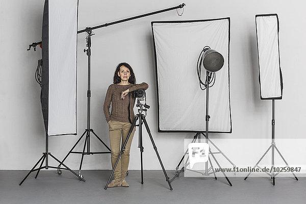 Volle Länge der selbstbewussten reifen Fotografin im Fotostudio