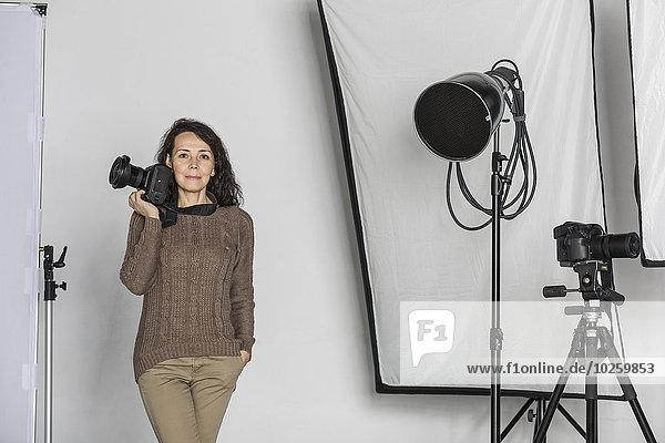 Portrait einer reifen Fotografin mit Kamera im Fotostudio
