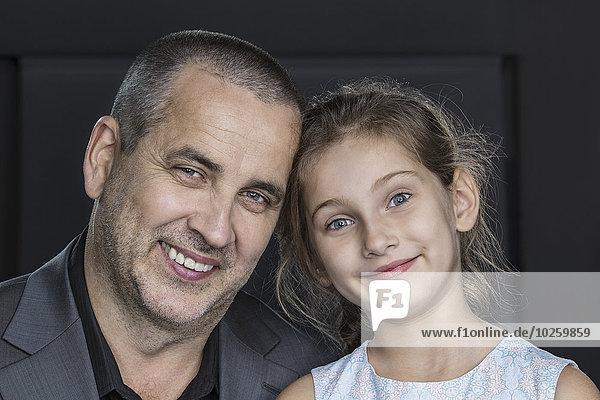 Nahaufnahme des glücklichen Vaters mit Tochter über grauem Hintergrund