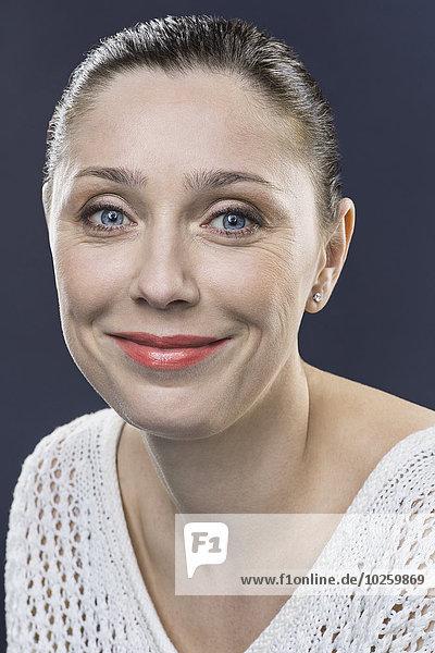 Nahaufnahme Porträt einer lächelnden erwachsenen Frau über grauem Hintergrund